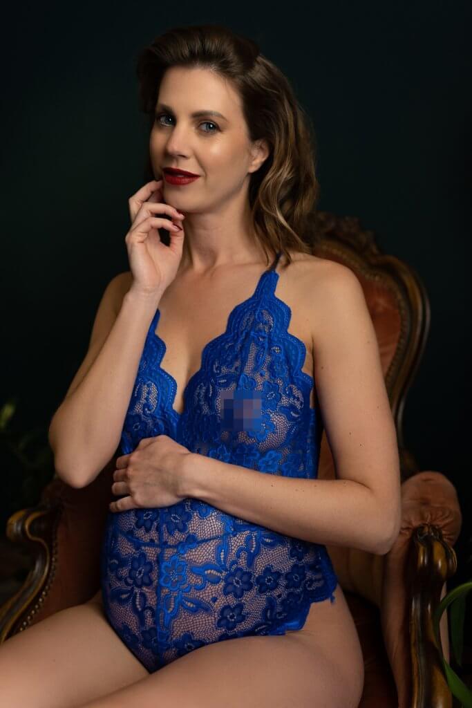 Zwangere vrouw blauwe bodysuit kijkt in camera