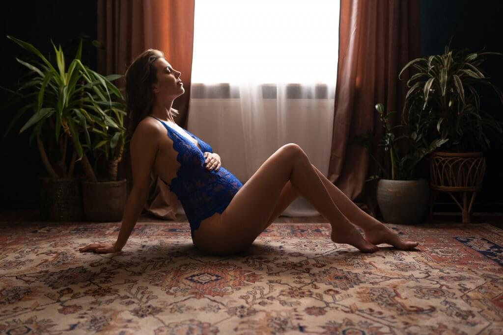 Zwanger vrouw in lingerie poseert op de vloer