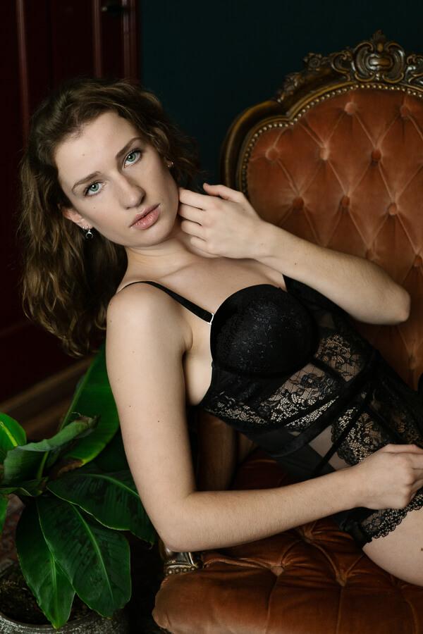 Vrouw in lingerie in stoel kijkt in camera