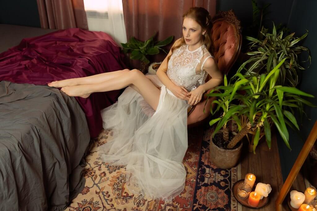 Bruid in lingerie en tule jurk op stoel