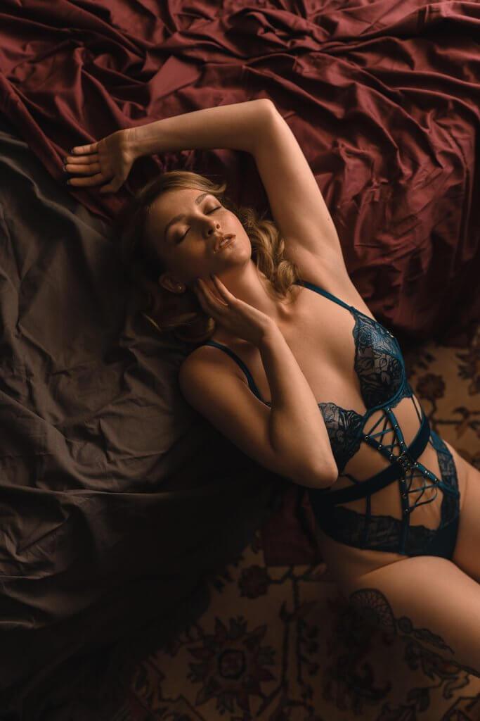 Lingerie fotografie vrouw ligt tegen bed