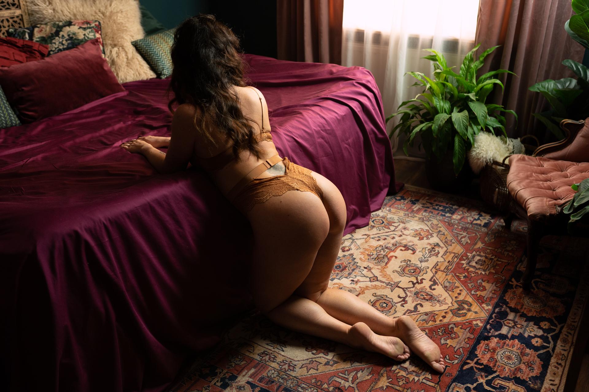 vrouw zit tegen bed aan boudoir fotografie